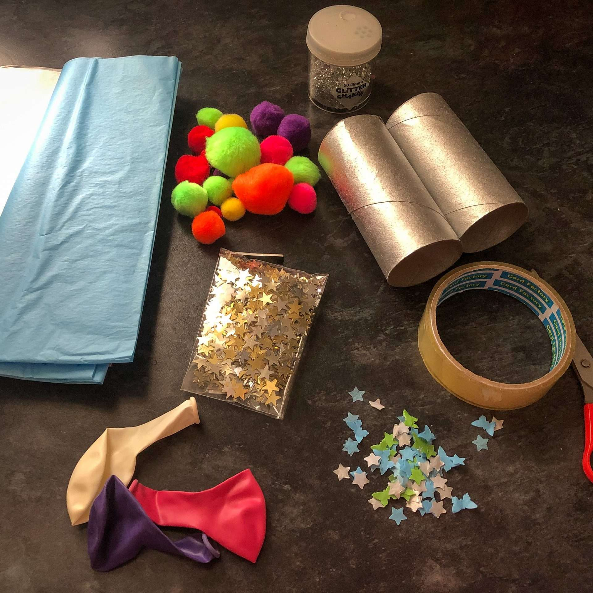 An assortment of arts and crafts are resting on a dark grey countertop. Items include tissue paper, pompoms, glitter, gold and silver stars, balloons