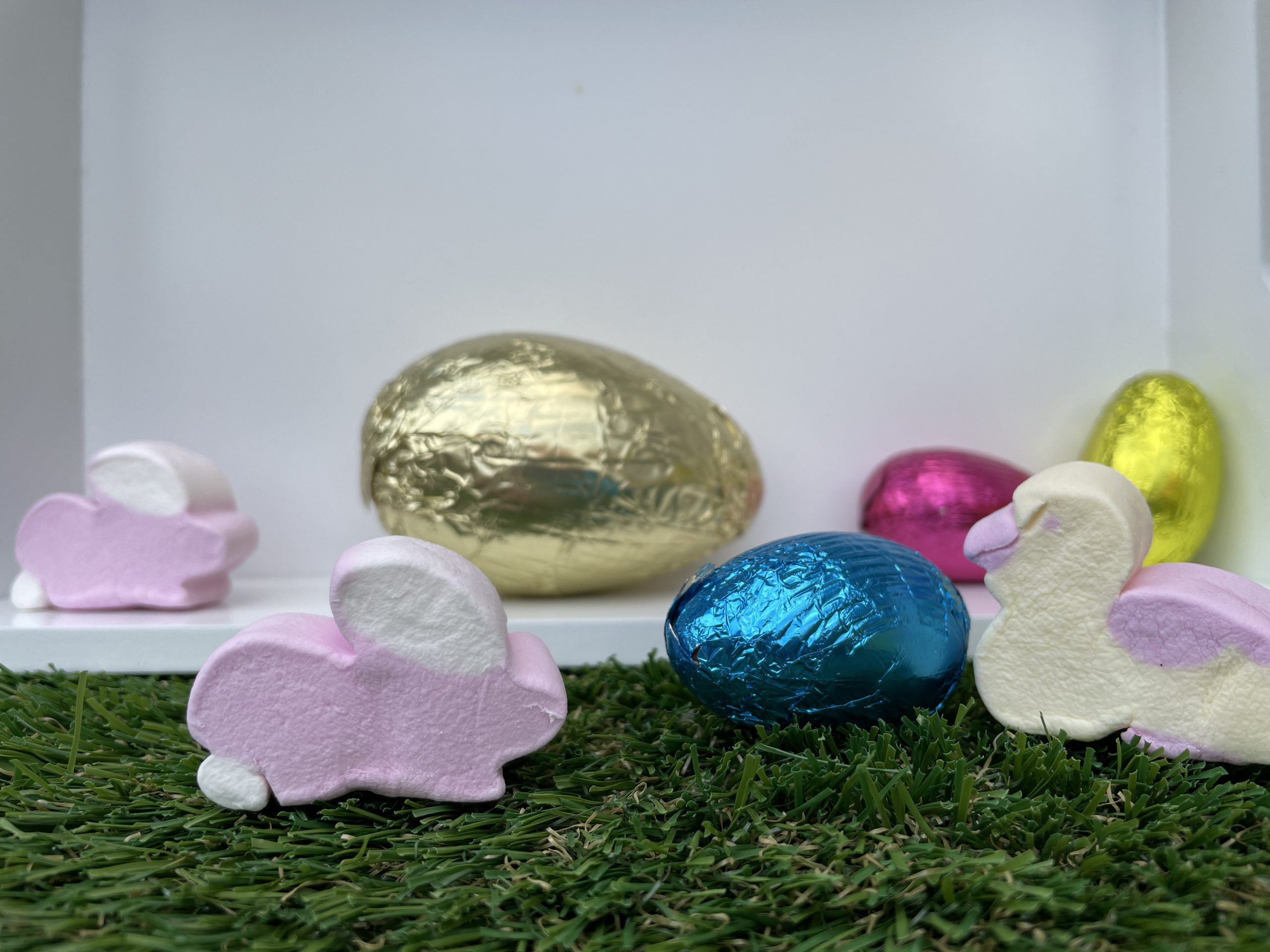 On a grass surface and white background are 2x pink and white marshmallow bunnies and 1x duck. There are 4 easter eggs, in gold, yellow, pink and blue