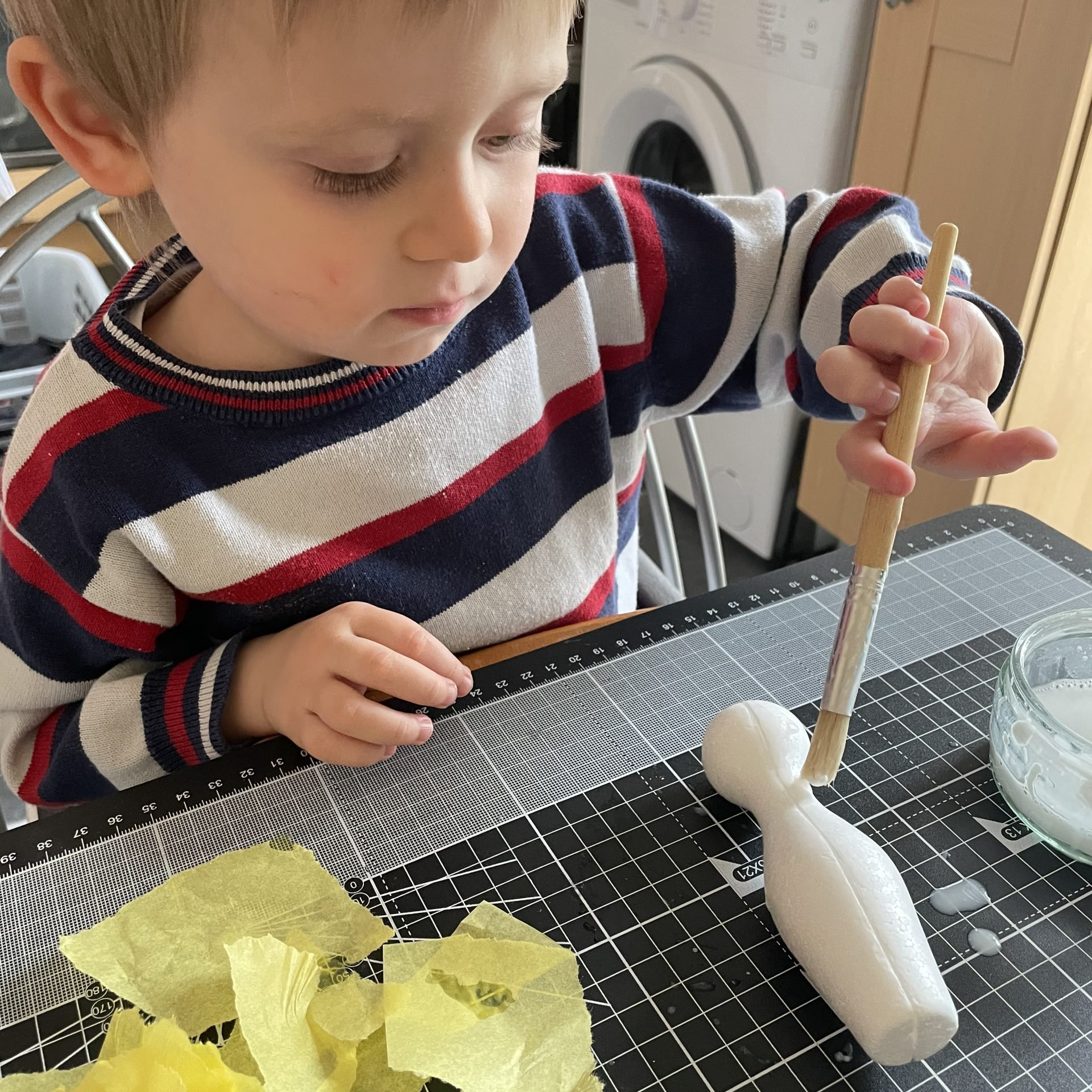 Little J is wearing a blue, white and red jumper. He is sat at a table with a checkered black and white mat in front of him. He is holding a paintbrush and brushing a small bowling Pin with a glue mixture. There is yellow tissue paper next to him