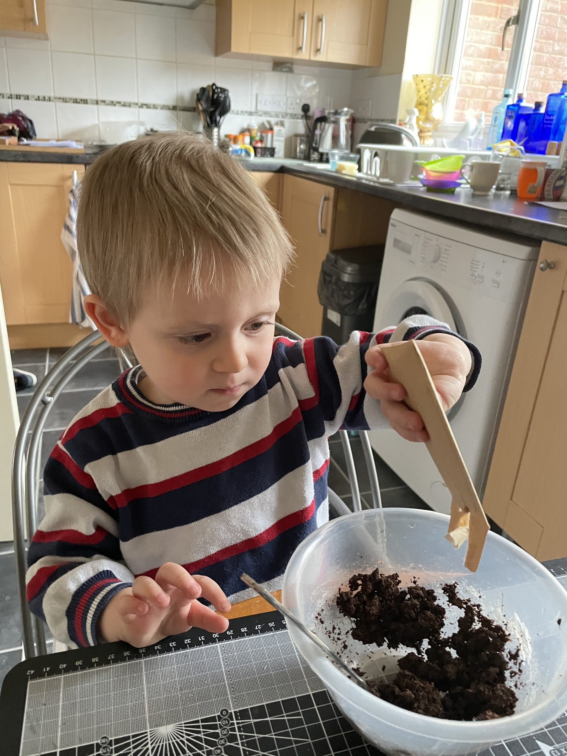Little J is wearing a white, red and blue jumper. He is sat at a table with a bowl in front of him. There is compost and clay in the bowl and he is adding wildflower seeds from a small brown packet