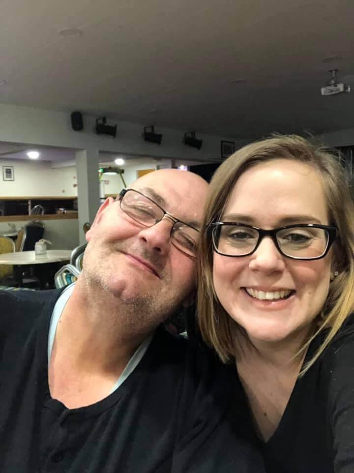 Lisa and her dad are both smiling at the camera. They are both wearing glasses and black t-shirts and Lisas dad is resting his head against hers