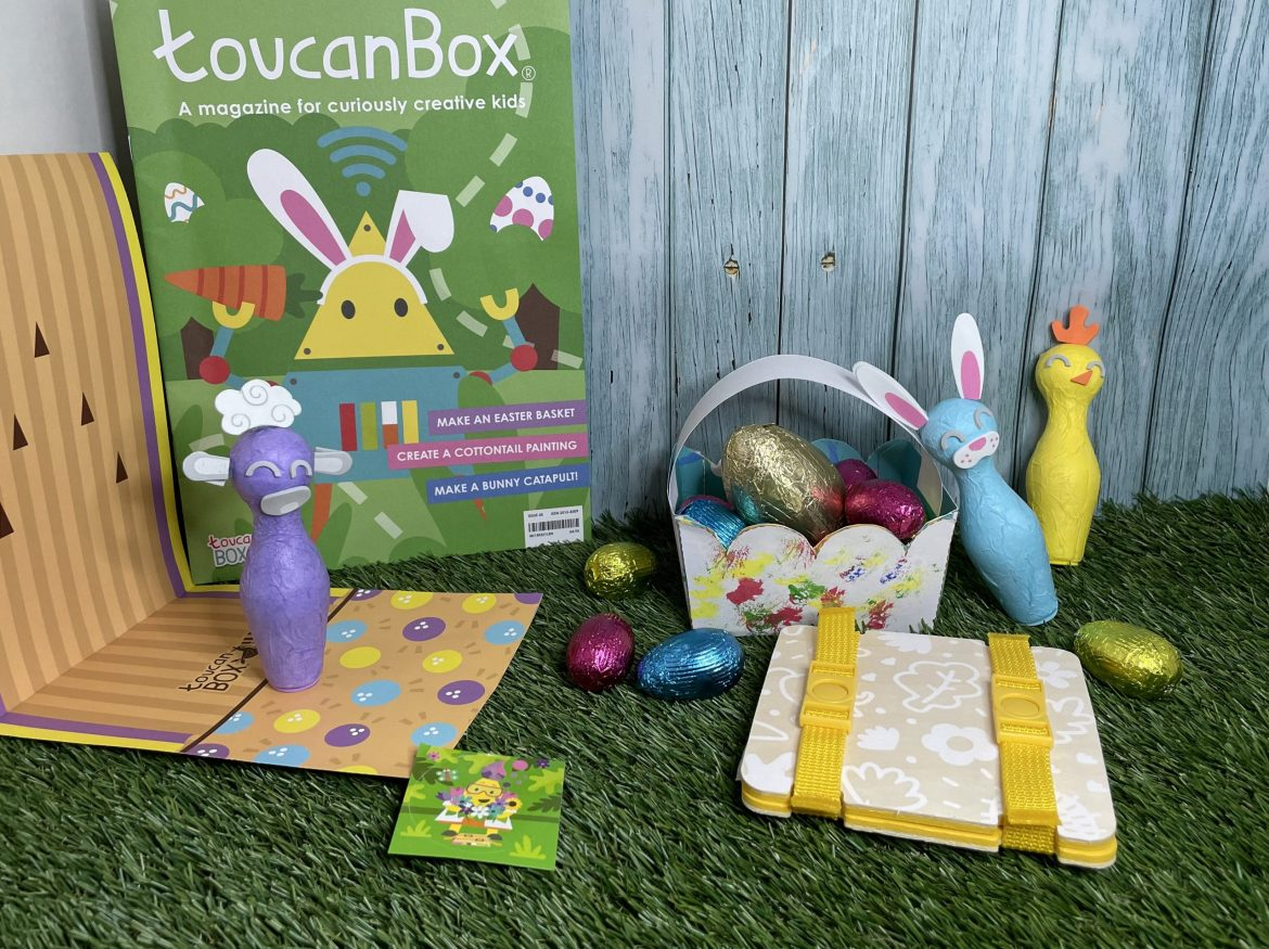 On a grass surface are - a handmade basket with pink, blue and gold egg, a yellow flower press, a toucanBox magazine, 3 small bowling pins in purple (a sheep), blue (a bunny) and yellow (a chick). There is a bowling ally made out of paper and a toucanBox sticker. It is all against a blue fence