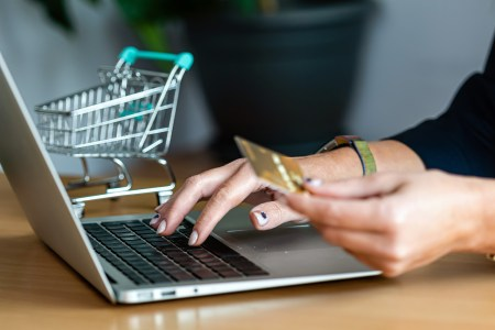 close-up of a woman hands buying online with a credit card and a laptop, e-commerce concept