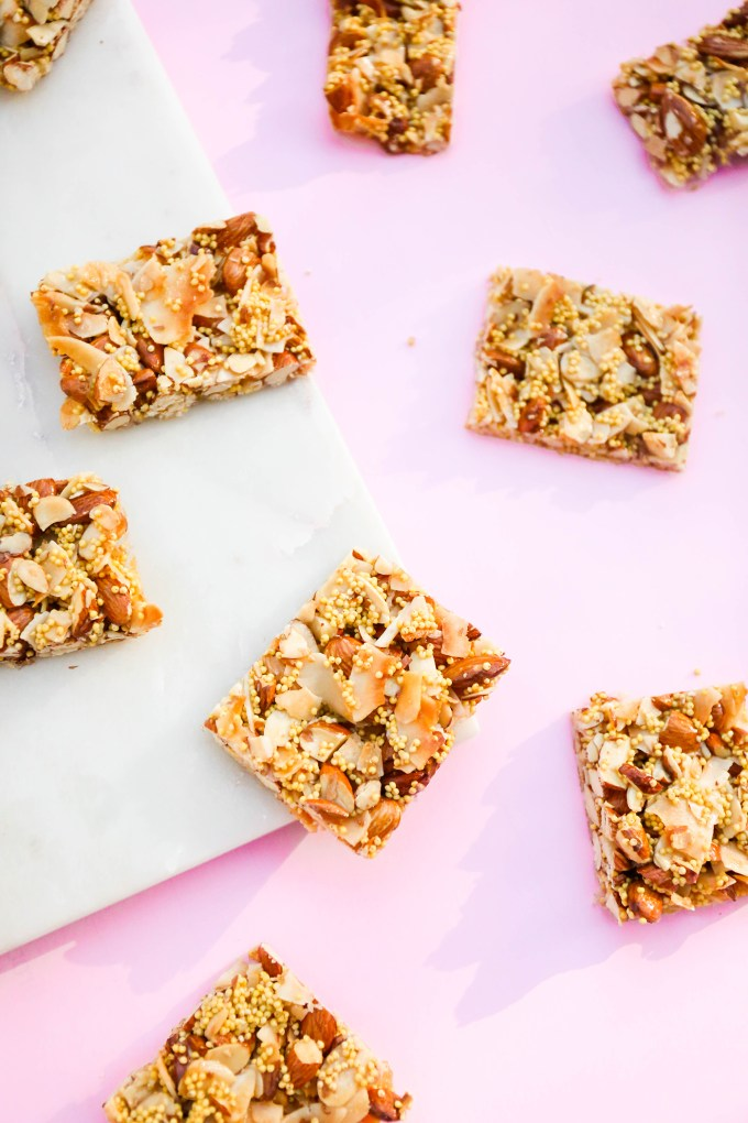 closeup of homemade granola bars sitting on pink and marble slab