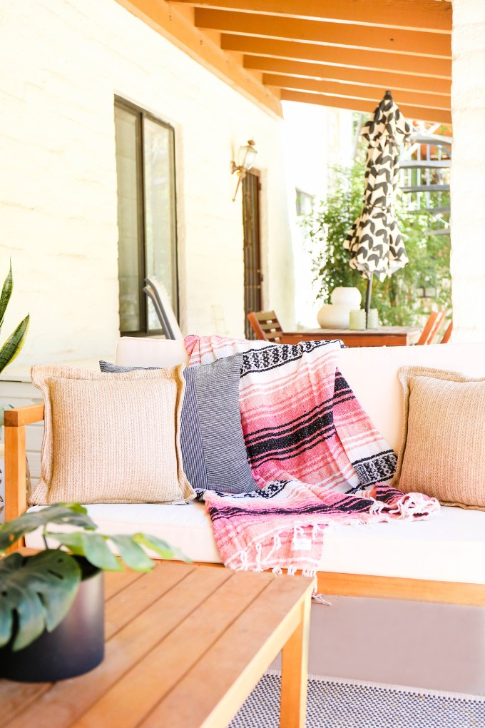 mexican blanket rests on modern white outdoor loveseat with throw pillow