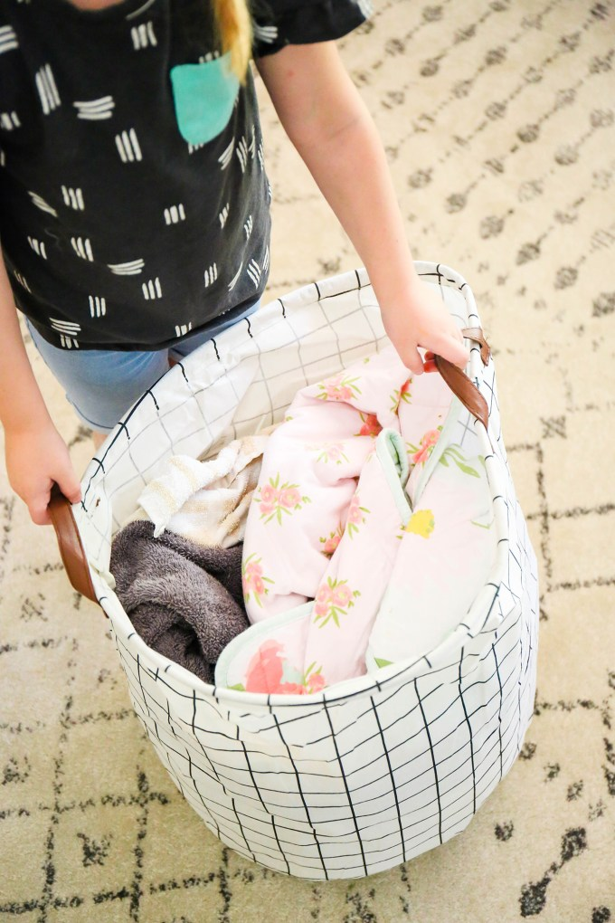 grid storage bin with laundry and blankets, being held by child