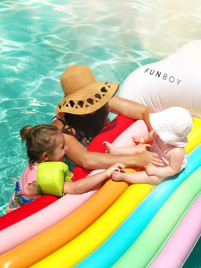 mom and daughters with rainbow pool float