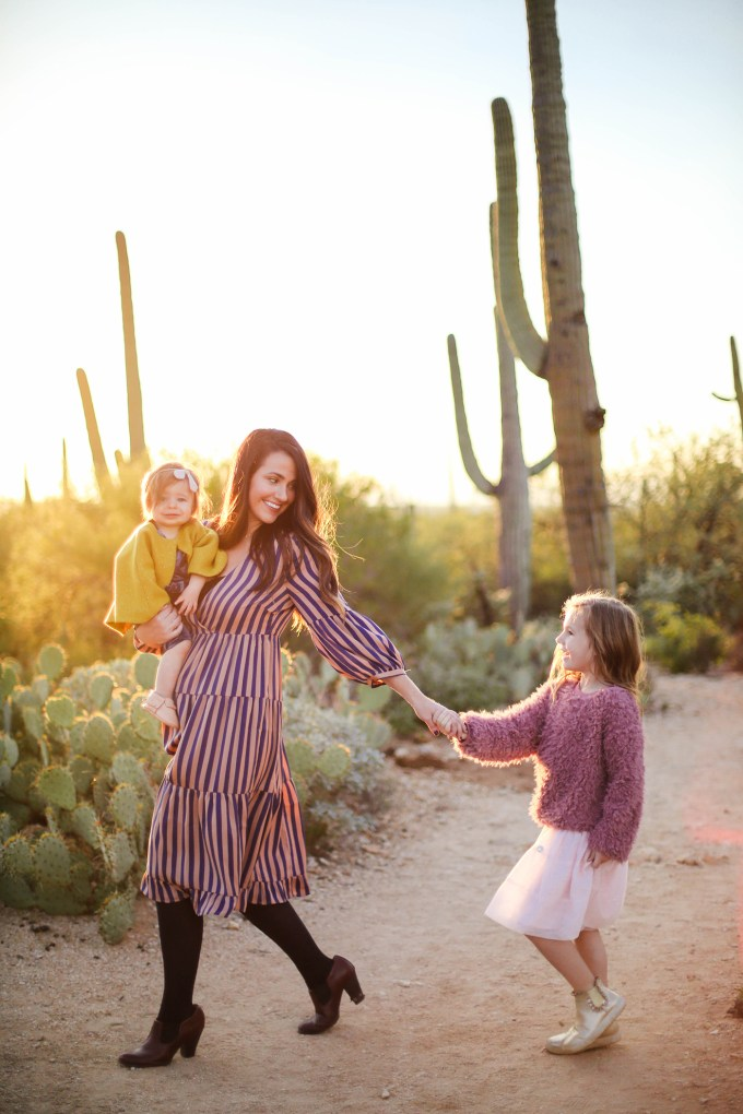 mom and daughters walk in desert