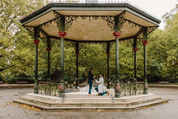 A Bandstand with a man on one knee proposing to a woman