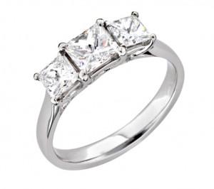 £7,500 Platinum diamond trilogy ring set with three graduated princess cut diamonds.