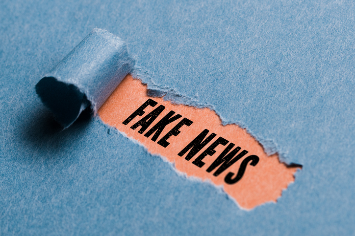 """torn paper revealing the phrase """"Fake News"""""""