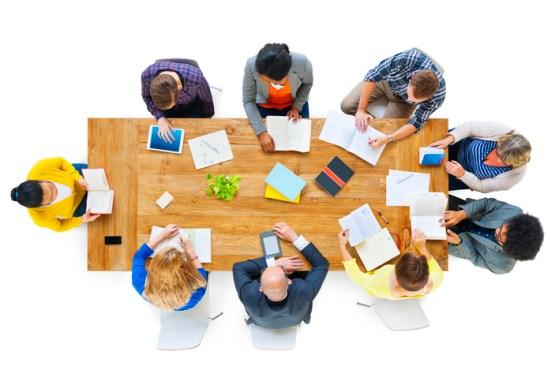Group of Business People Reading Notes on a Meeting Table