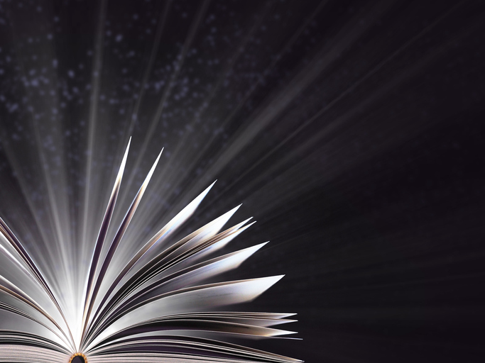 Part of an open magic book, bewitched book glows in the darkness, magic light. Education. Dreamy image of a fairytale