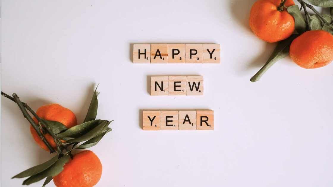 Happy New Year Quiz. Scrabble tiles with oranges on a white background.
