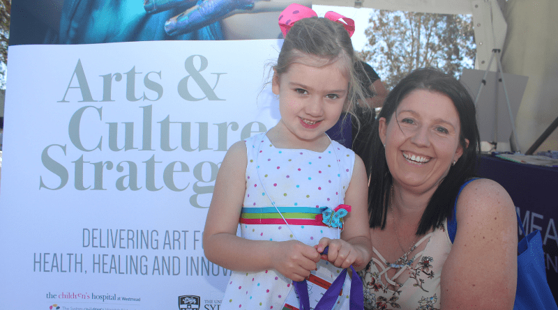 girl and woman smile to camera in front of pull-up banner which says Arts & Culture Strategy
