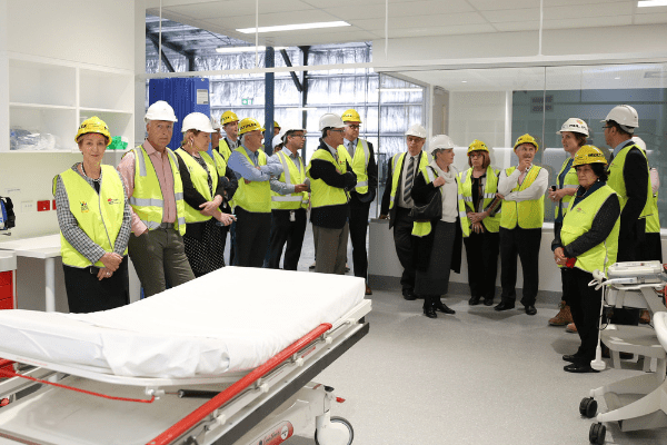 group in high vis vests and helmets inside prototype room which includes a patient bed