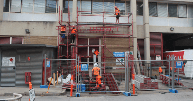 Construction workers installing hoist next to building