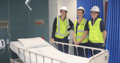 Three women in hi-vis vests and helmets smile to camera next to patient bed