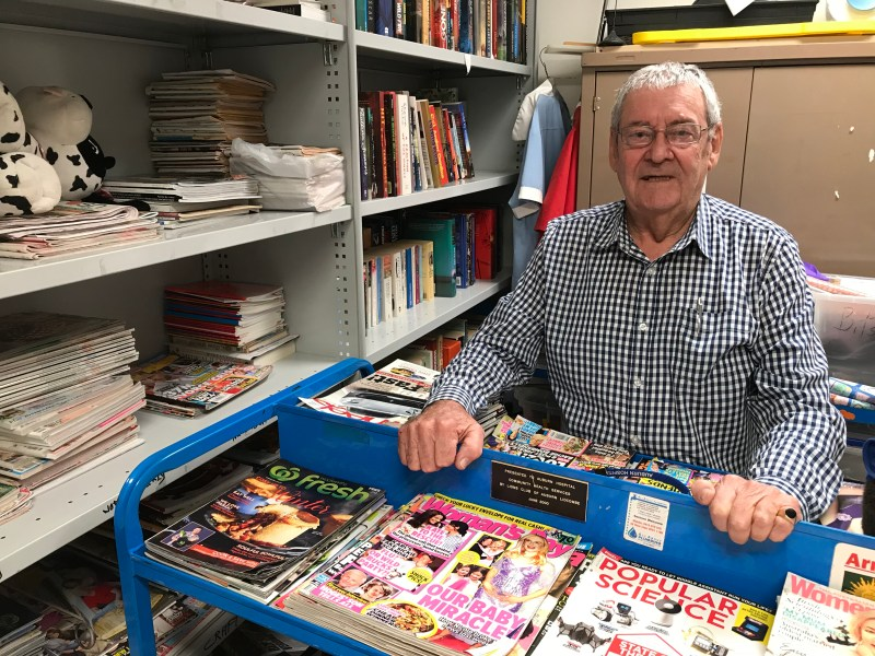 A smiling older man stands in a room filled with books and magazines