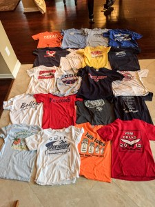 A colorful collection of t-shirts arranged on the floor in preparation to be sorted for a t-shirt quilt