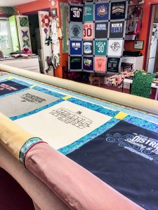 A longarm quilting machine is used to quilt together the top made from t-shirts