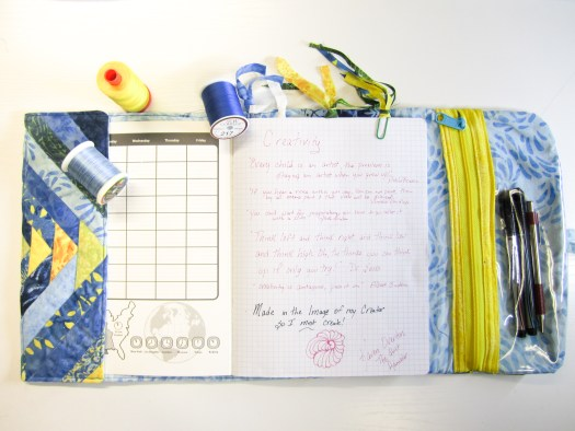 A composition notebook covered in quilted fabric is opened to show the hidden extra of a zippered pen pouch