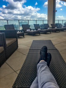 Lady's jean clad legs stretched out in relaxation overlooking a pool area on top of a Houston motel showing beautiful clouds and building in the distance