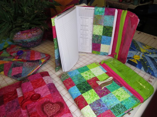 Quilted covers include a vinyl zippered pocket for pens and a button closure