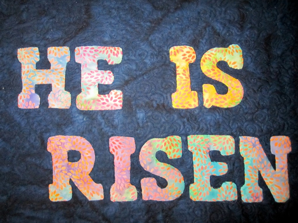 """Close up of quilted reverse appliqué lettering saying """"He is Risen"""""""