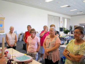 ladies carefully watching a quilting workshop demonstration