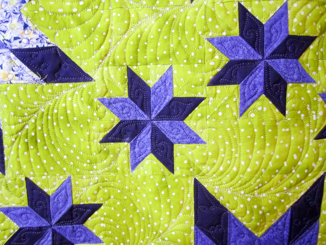 close up of quilting around small 8 pointed stars