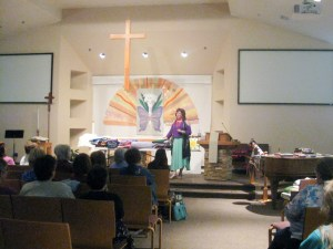 A lady at the front of a church with a table full of folded quilts ready for show and tell