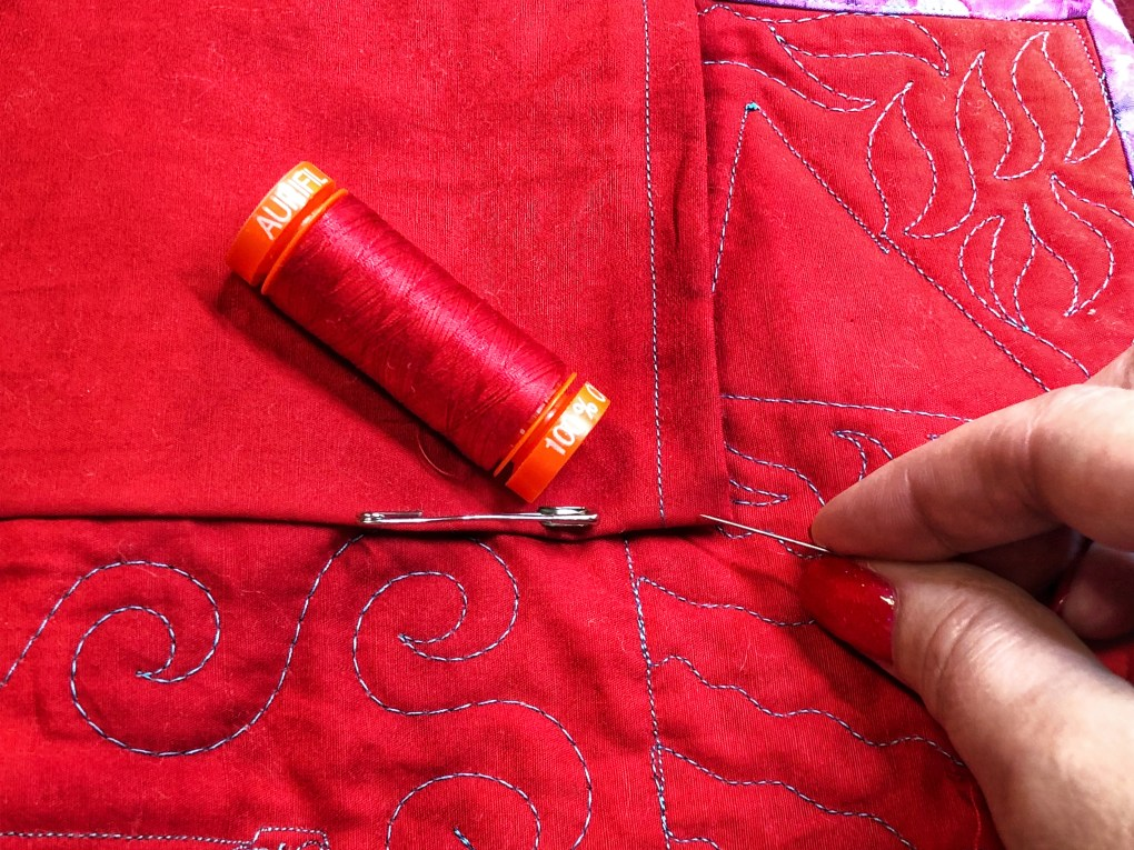 Red Aurifil thread matches the fabric perfectly for hand sewing a hanging sleeve on the back of a quilt