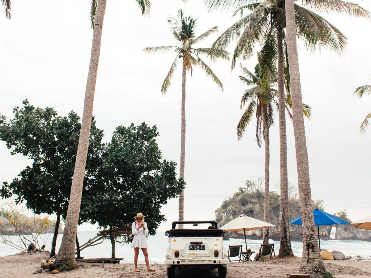 unrecognizable woman near car on tropical beach