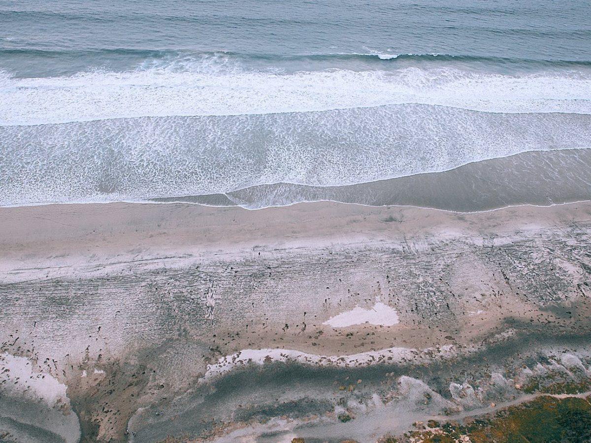 coast against foamy ocean with fast water flows