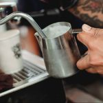 crop faceless barista frothing milk with steam wand
