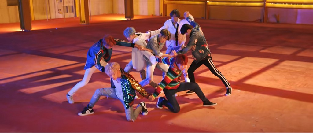 The seven members of BTS join hands to form a formation that resembles a double-helix