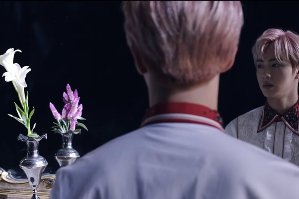 A man gazes into a mirror where the reflection of a vase of white flowers appears as a vase of purples flowers