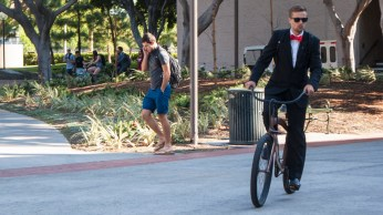 A USC student rides his bike while sporting a suit.