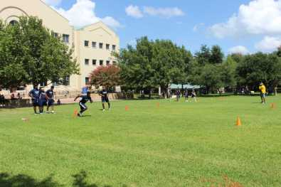 Wesleyan football player runs through the cones at practice.