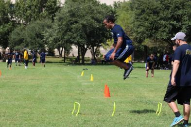 Wesleyan player jumps over hurdles at the first practice.