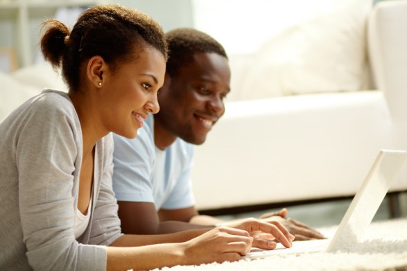 Young black couple on computer, smiling. Signifies feeling connected and with better communication skills after attending an online hold me tight program for couples.