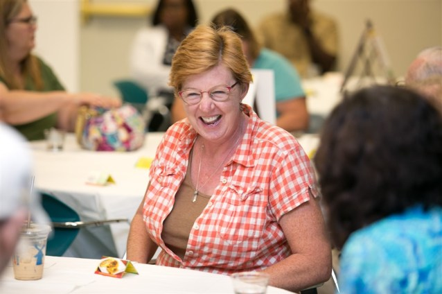 A laughing white woman with red hair at an event catered by Rasta Mama's Kitchen.