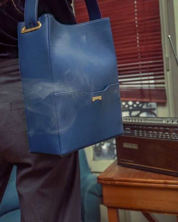 Luxury Parisian flat with smoke and a model with a dark blue vegan leather bucket bag