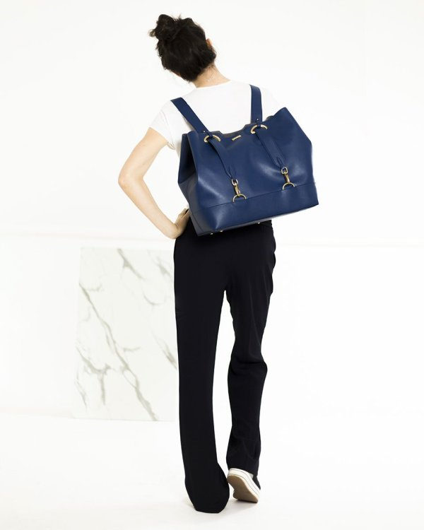 Model wearing navy blue ecofriendly vegan leather handbag