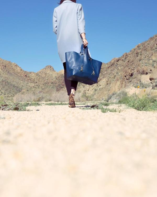 Model walking in the desert with a navy luxury vegan handbag