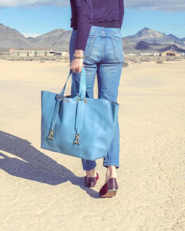 Model wearing light blue ecofriendly vegan leather handbag in the desert