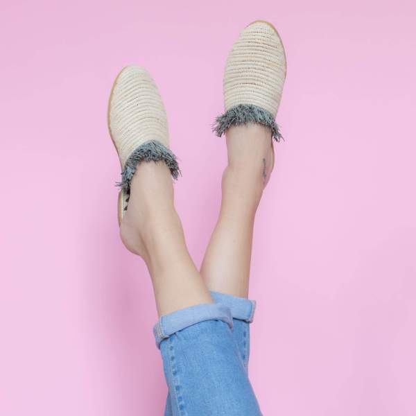 feet model in front of a pink background wearing jeans and abury beige raffia summer slippers with fringes