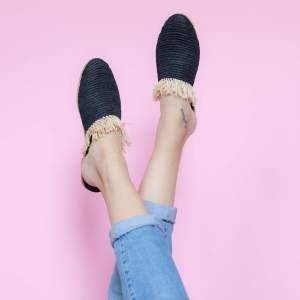 feet model in front of a pink background wearing jeans and abury black raffia summer slippers with fringes