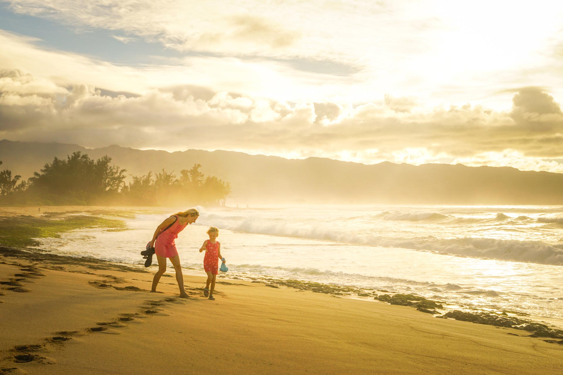 thereafterish feature photo of Caucasian woman and daughter walking along a beach during golden hour